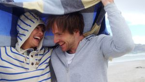 Happy couple hiding in blanket at beach