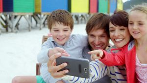 Happy family using mobile phone at beach