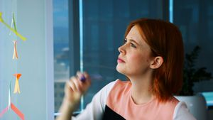 Female executive writing over sticky note on glass board