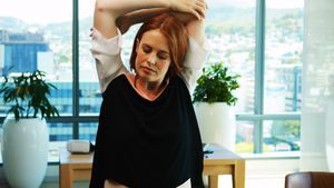 Female executive doing stretching exercise at her desk