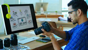 Male graphic designer looking at photos in digital camera at his desk