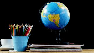 Globe and school supplies on table