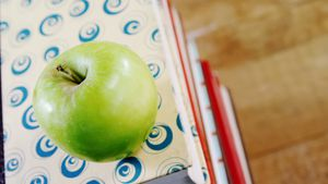 Green apple on book stack