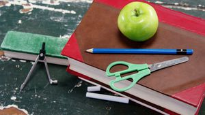 Green apple on book stack with school supplies