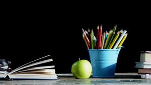 Green apple and school supplies on table
