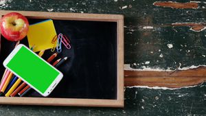 Apple and mobile phone with school supplies on slate