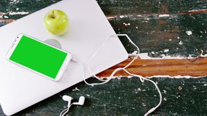 Mobile phone and green apple on laptop