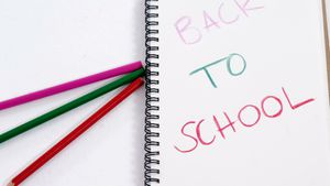 Back to school text on open diary with colored pencils