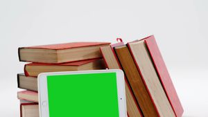 Stack of books with digital tablet against white background