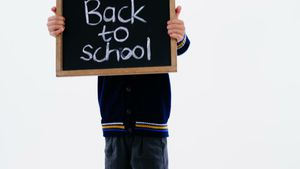 Schoolboy holding chalkboard with back to school text