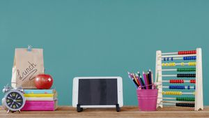 School accessories with digital tablet, lunch and alarm clock on table