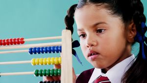 Cute little girl counting on abacus