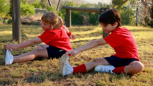 Kids performing stretching exercise in boot camp