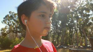 Determined boy listening song while walking on obstacle