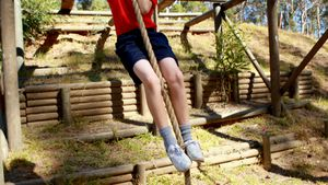 Determined girl climbing rope during obstacle course