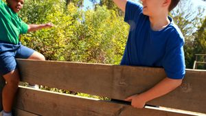 Kids cheering on wooden wall during obstacle course