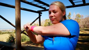 Determined woman performing stretching exercise during obstacle course