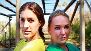 Portrait of confident friends standing back to back during obstacle course