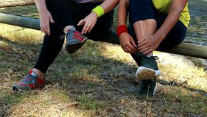 Low section of women tying shoe lace during obstacle course