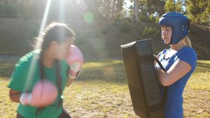 Determined women practicing boxing during obstacle course