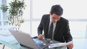 A business man uses a calculator to check his spreadsheet
