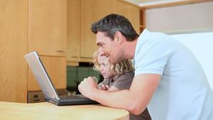 Father and son are using a laptop