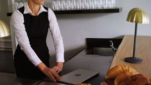 Waitress walking with laptop at counter