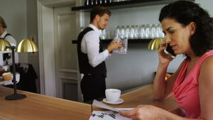 Woman sitting at bar counter talking on mobile phone