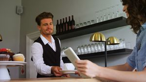Waiter serving coffee to costumer at counter