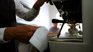 Waiter wiping a espresso machine at counter