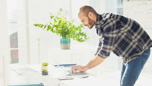 Male executive working on laptop at desk