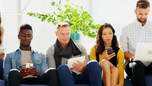Business colleagues using electronic devices while sitting on sofa