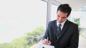 Businessman writing on a notepad