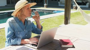 Senior woman using laptop near swimming pool