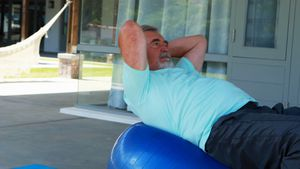 Senior man exercising on fitness ball doing crunches