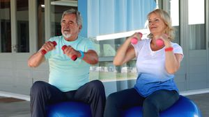 Senior couple exercising with dumbbell on exercise ball