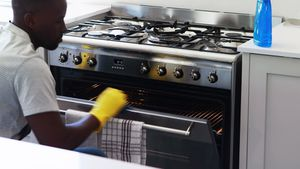 Man cleaning the oven in kitchen