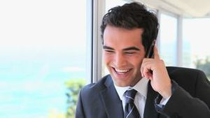 Smiling man in suit on the phone