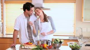 Husband tasting his wifes cooking with a spoon