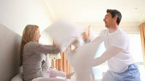 Young family having a pillow fight