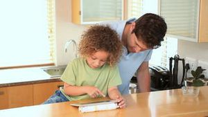 Boy using a ebook with his father