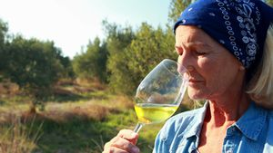 Woman examining glass of wine 4k