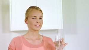 Portrait of smiling woman drinking water