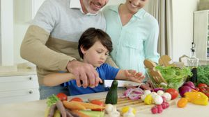 Parents assisting son in chopping vegetable