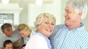 Smiling senior couple standing with arm around at home