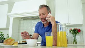 Man talking on mobile phone while having breakfast on dining table