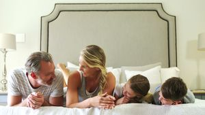 Family lying together in bedroom at home 4k
