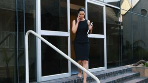 Businesswoman talking on mobile phone and walking out of office building 4k
