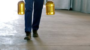 Worker walking with can of olive oils in factory