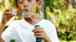 Boy blowing bubble with wand